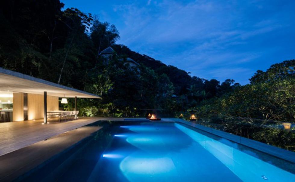Swimmingpoolen på husets trädäck i månskenet.